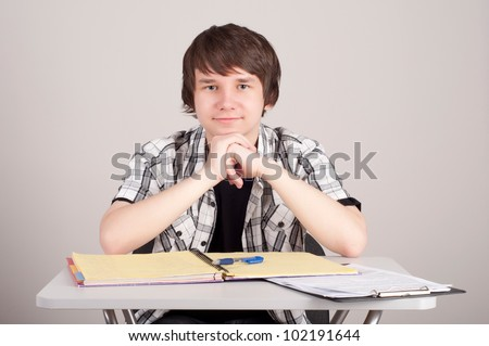 student in exams, sits at the table and reading a book - stock photo