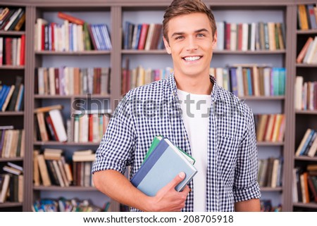 Student in library. Handsome young man holding books and smiling while standing in library - stock photo