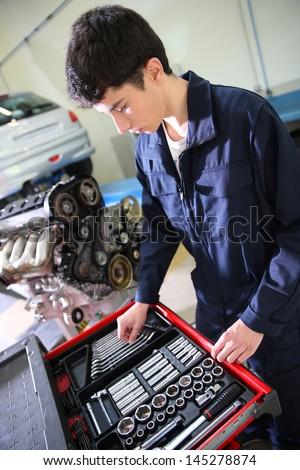 Student in mechanics working on car engine - stock photo