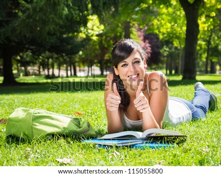 Student in park with thumbs up. Happy university woman student stufying outdoor lying on grass. Copy space. - stock photo