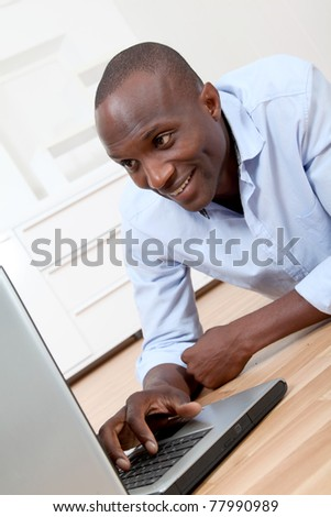 Student in room with laptop computer - stock photo