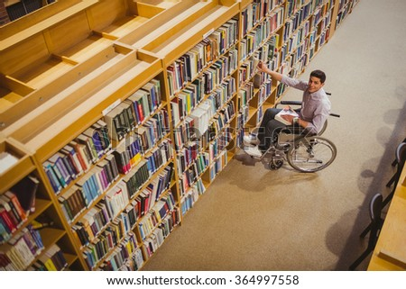 Student in wheelchair picking a book from shelf in library - stock photo