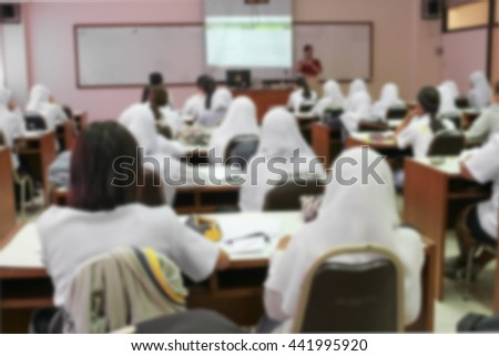 student learning  business sitting  in room  with teacher front and white projector slide screen Blur blurred view  from back of the classroom - stock photo