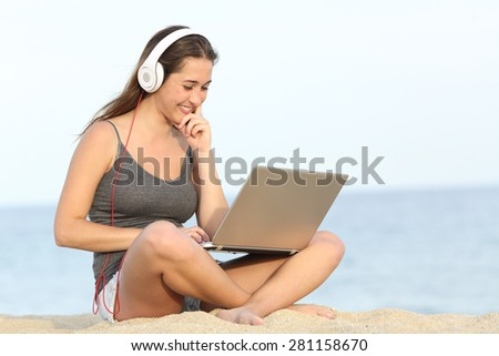 Student learning course online with a laptop and headphones sitting on the beach near the sea