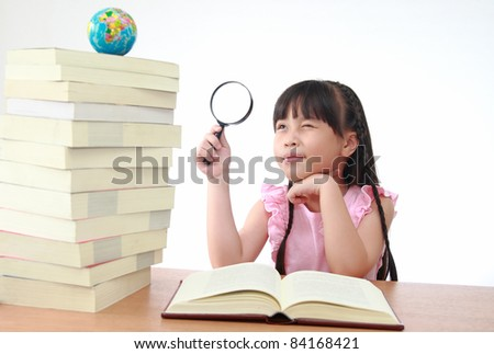 Student little asian girl reading with magnifying glass look the globe