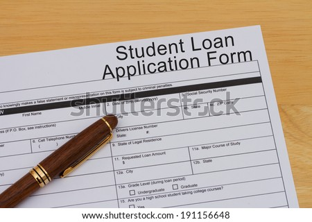 Student Loan Application Form with a pen on a wooden desk - stock photo