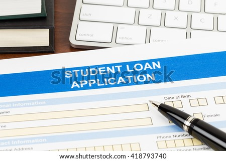 Student loan application form with pen, keyboard, and text book - stock photo
