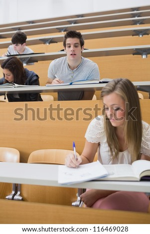 Student looking at another students work sneakily in lecture hall - stock photo