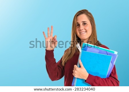 Student making Ok sign over colorful background - stock photo