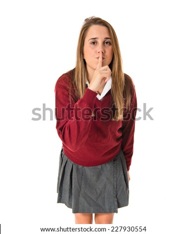 Student making silence gesture over isolated white background - stock photo