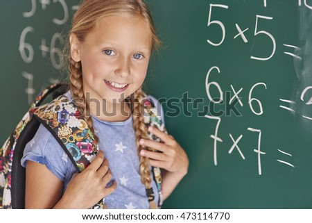 Student next to blackboard with numbers