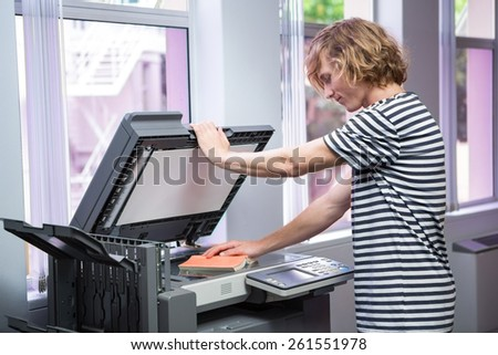 Student photocopying his book in the library at the university - stock photo