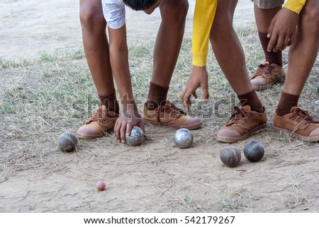 Student  playing petanque in a school, detail of balls, legs in background