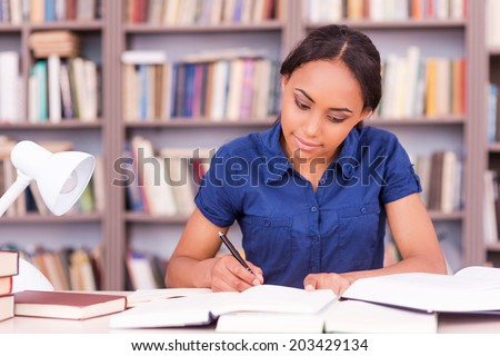 Student preparing to the exams. Confident young black woman writing something in her note pad and reading book while sitting at the library desk - stock photo