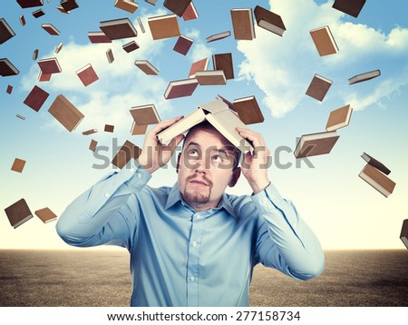 student protect himself from book rain - stock photo