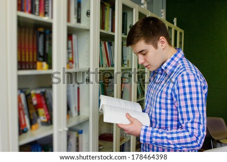 student reading book at the public library  - stock photo