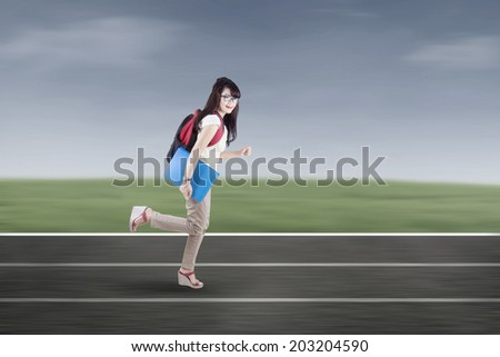 Student running on tracks. shot outdoors - stock photo