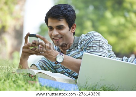 Student sending a text message on mobile phone - stock photo