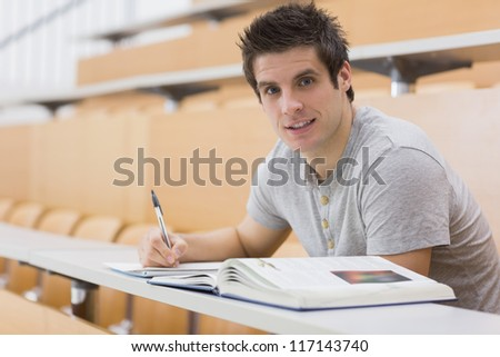 Student sitting at the desk while smiling in lecture hall