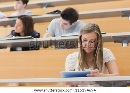 Student sitting at the lecture hall while holding a tablet pc and usig it to take notes - stock photo