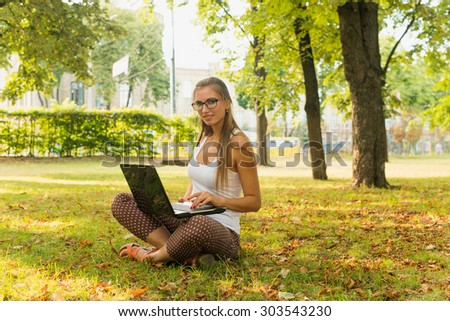 Student sitting in park near the grass working on laptop at campus