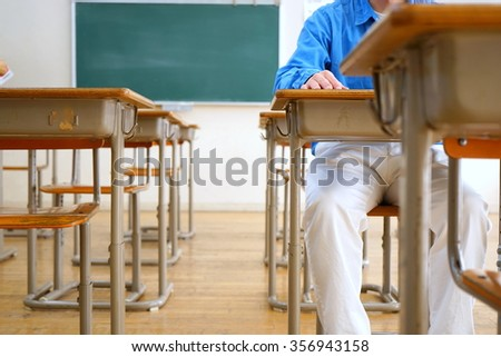 student sitting on a chair in the classroom - stock photo