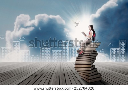 Student sitting on a stack of books while looking at flying dove - stock photo