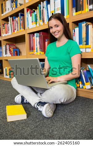 Student sitting on floor in library using laptop at the university - stock photo