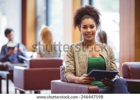 Student sitting on sofa using her tablet pc smiling at camera at the university - stock photo
