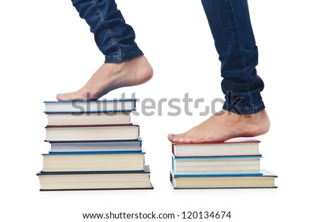 Student sitting on stack of books - stock photo