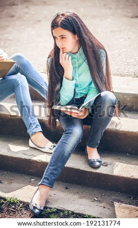 student sitting with a book on street - stock photo