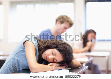 Student sleeping on her desk in a classroom - stock photo