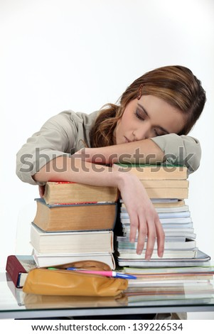 student sleeping over a pile of books - stock photo