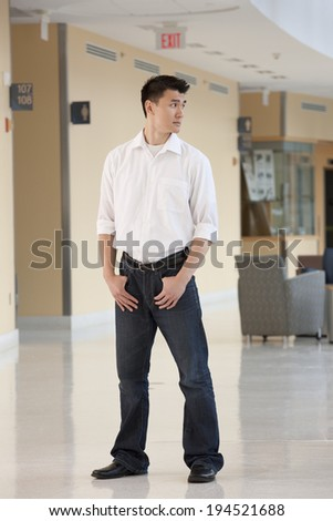 Student standing in college hallway with hands in pockets - stock photo