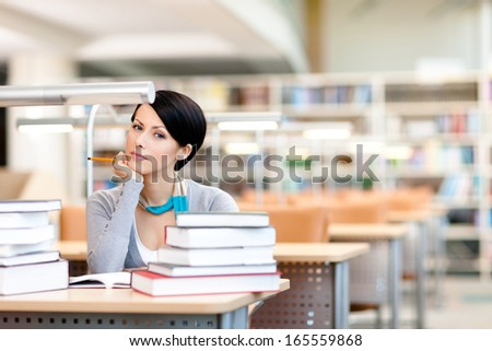 Student studies with piles of books sitting at the table at the reading hall - stock photo