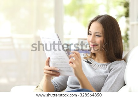 Student studying and learning reading notes siting on a couch in the living room at home - stock photo