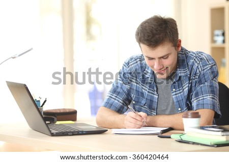 Student studying and writing notes in a notebook sitting at a desk at home - stock photo