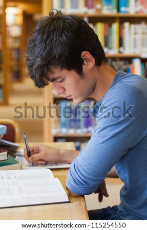 Student studying at desk in college library - stock photo