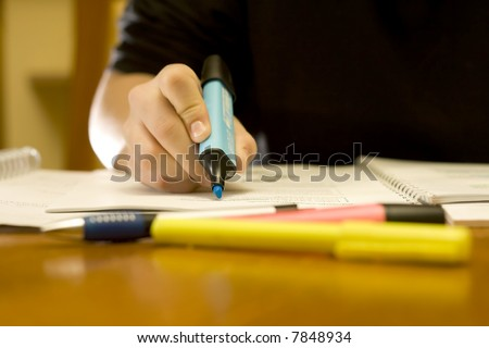 Student studying in a library using a blue marker to mark important notes. Studio lighting.