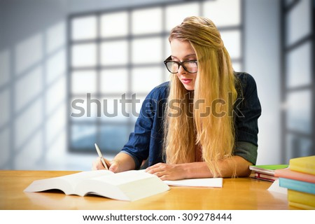 Student studying in the library against room with large windows showing city - stock photo