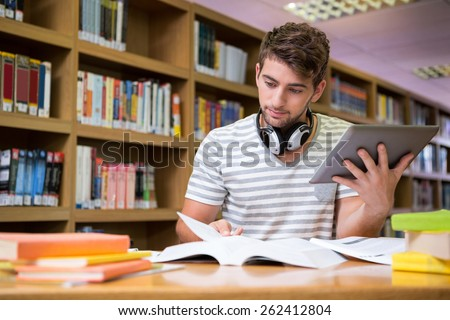 Student studying in the library with tablet at the university - stock photo