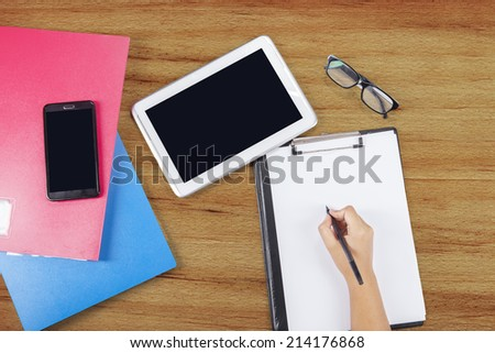 Student studying with digital tablet, smartphone, folder, and clipboard - stock photo