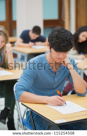 Student taking exam in exam hall in college - stock photo