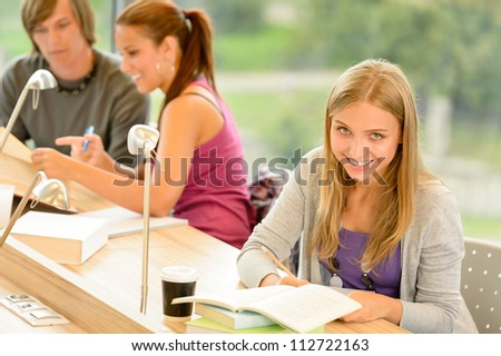 Student taking notes in study room smiling education campus