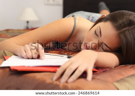 Student tired and sleeping in her bed room over the notes while was studying - stock photo