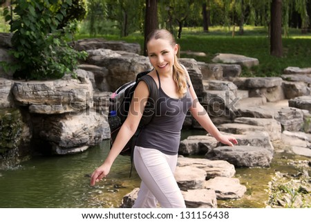 Student  travel at countryside during summer holidays. Woman hiking in jungle with backpack and crossing river in nature - stock photo
