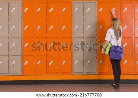 Student unlocking school locker - stock photo