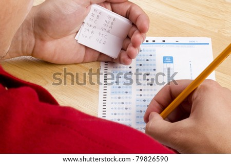 Student using a cheat sheet to cheat on his test. - stock photo