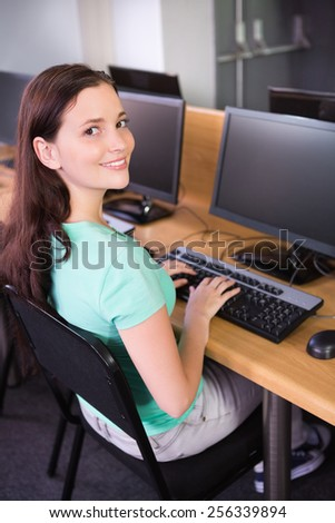 Student using computer in classroom at the university - stock photo