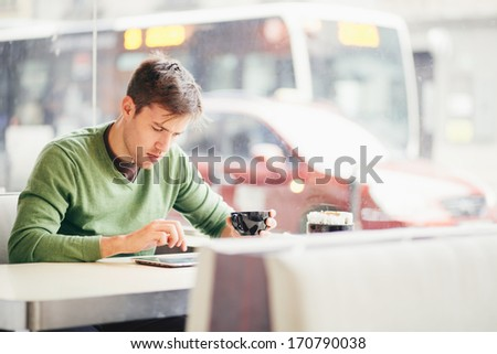 Student using tablet computer in cafe - stock photo